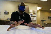 Larry Brown moves his fingers during his occupational therapy session at Community Health Network, Thursday, Aug. 20, 2020, in Indianapolis. Hand therapy is twice a week. His hands, once making savvy plays on game days when he was an Indiana State football player, are now shaky when he snags a medicine ball bounced off a trampoline. (AP Photo/Darron Cummings)