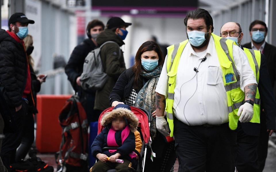 A family arriving at Edinburgh Airport from Turkey are escorted to a quarantine hotel on February 15 -  Getty Images Europe/Getty