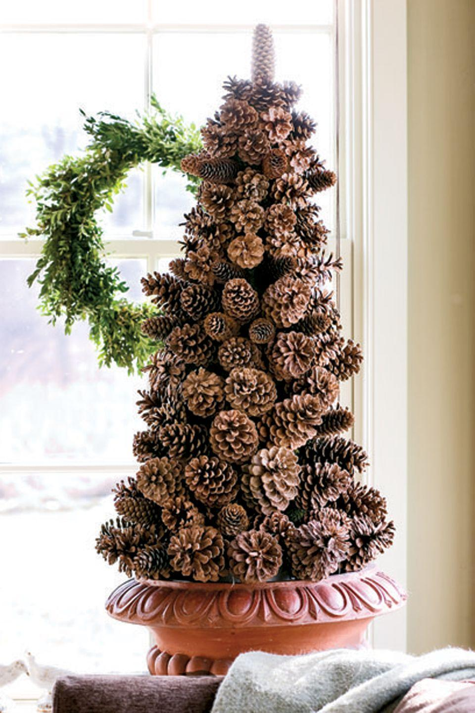 """<p>Create a pinecone tree on a cone-shaped foam base. Anchor the base in a container, then wire the cones onto 2"""" wooden floral picks. Insert picks downward into the foam, starting at the bottom with the largest cones and working to the top with the smaller ones. Conceal the foam by tucking sheet moss among the pinecones.</p><p><a class=""""link rapid-noclick-resp"""" href=""""https://www.amazon.com/s/ref=nb_sb_noss_1?url=search-alias%3Daps&field-keywords=+cone-shaped+foam&rh=i%3Aaps%2Ck%3A+cone-shaped+foam&tag=syn-yahoo-20&ascsubtag=%5Bartid%7C10050.g.1247%5Bsrc%7Cyahoo-us"""" rel=""""nofollow noopener"""" target=""""_blank"""" data-ylk=""""slk:SHOP FOAM CONES"""">SHOP FOAM CONES</a> </p>"""
