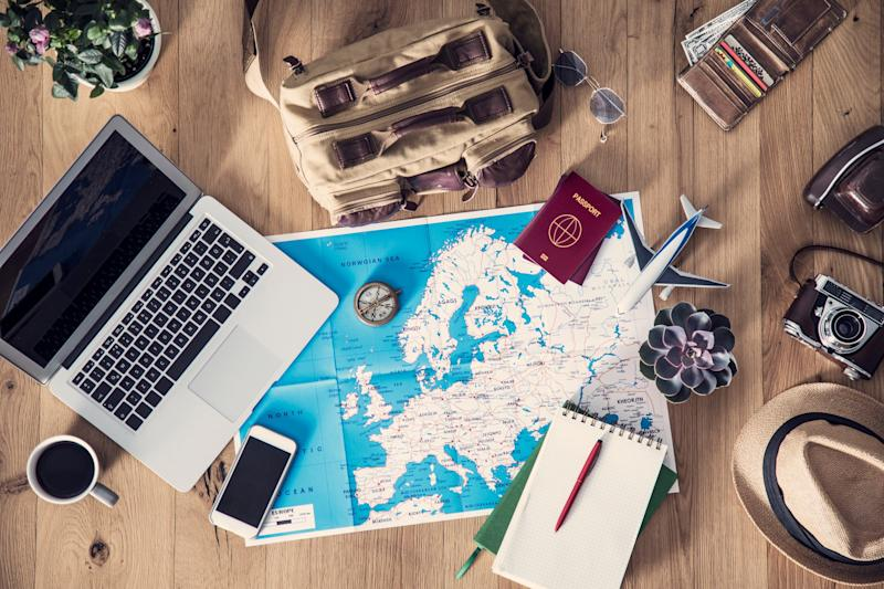 Map of Europe on a table with laptop, notebook, camera, passport, and other travel gear