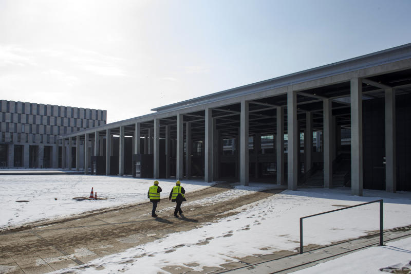 In this March 14, 2013 photo, two men walk to the main terminal of the new  Berlin Brandenburg International  Airport (BER) named Willy-Brandt-Flughafen in Schoenefeld near Berlin. Willy Brandt International Airport, named for Germany's famed Cold War leader, was supposed to have been up and running in late 2011, a sign of Berlin's transformation from Cold War confrontation line to world class capital of Europe's economic powerhouse. Instead it has become a symbol of how, even for this technological titan, things can go horribly wrong. After four publicly announced delays, officials acknowledged the airport won't be ready by the latest target: October 2013. To spare themselves further embarrassment, officials have refused to set a new opening date. (AP Photo/Markus Schreiber)