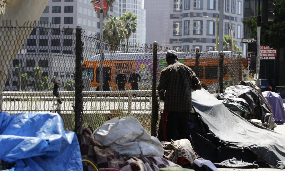 """<span class=""""element-image__caption"""">Los Angeles police officers guard a freeway ramp near a newly displaced homeless camp during Donald Trump's recent visit.</span> <span class=""""element-image__credit"""">Photograph: Damian Dovarganes/Associated Press</span>"""