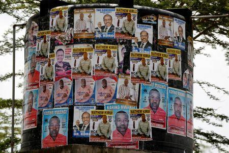 Campaign posters of candidates for the role of local representative are seen on a water tank in the Barut ward, Nakuru