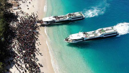 Boats arrive at shore to evacuate people on the island of Gili Trawangan, Lombok, Indonesia, August 6, 2018, in this still image taken from a drone video obtained from social media. Melissa Delport/@trufflejournal/via REUTERS