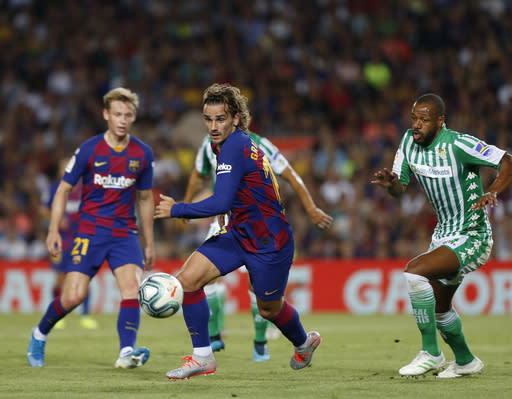 Barcelona's Antoine Griezmann, center, controls the ball during the Spanish La Liga soccer match between FC Barcelona and Betis at the Camp Nou stadium in Barcelona, Spain, Sunday, Aug. 25, 2019. (AP Photo/Joan Monfort)