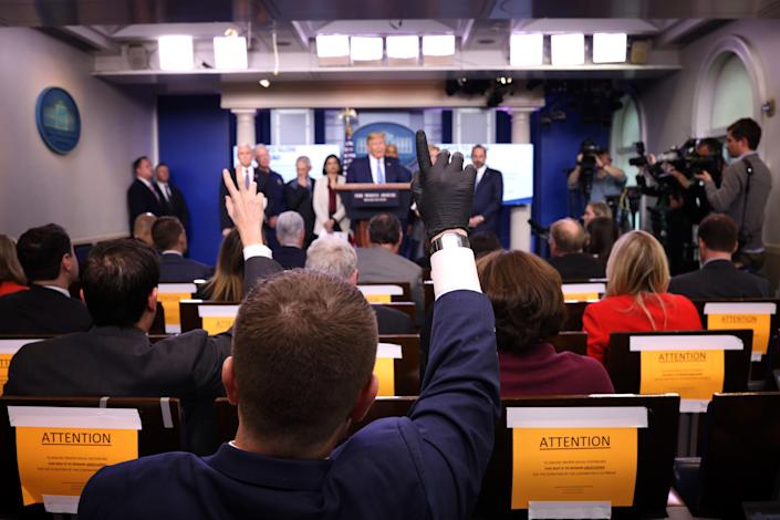 WASHINGTON, DC - MARCH 16: A reporter wearing a latex glove raises his hand to ask U.S. President Donald Trump a question during Coronavirus briefing at the White House on March 16, 2020 in Washington, DC. The United States has surpassed 3,000 confirmed cases of the coronavirus, and the death toll climbed to at least 61, with 25 of the deaths associated with the Life Care Center in Kirkland, Washington. (Photo by Win McNamee/Getty Images)