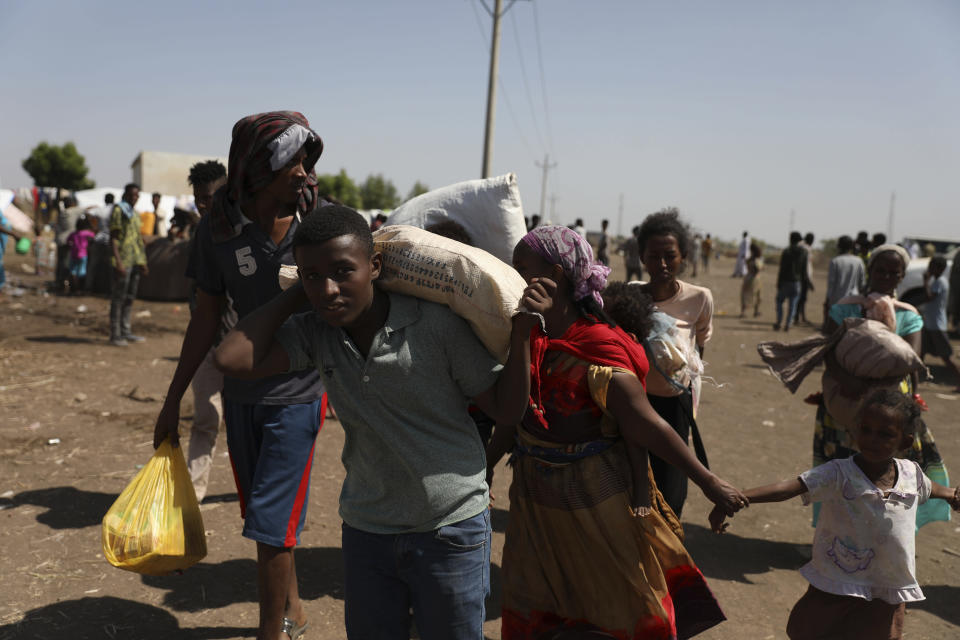 Refugees from the Tigray region of Ethiopia arrive at Hamdayet, Sudan on Saturday, Nov. 14, 2020. Many are waiting to register at the UNCHR center. Ethiopia's defiant Tigray regional government has fired rockets at two airports in the neighboring Amhara region as a deadly conflict threatens to spread into other parts of Africa's second-most populous country. (AP Photo/Marwan Ali)