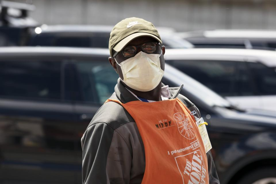 A Home Depot employee wears a protective mask while on the job, Saturday, April 11, 2020, in Somerville, Mass. (AP Photo/Michael Dwyer)
