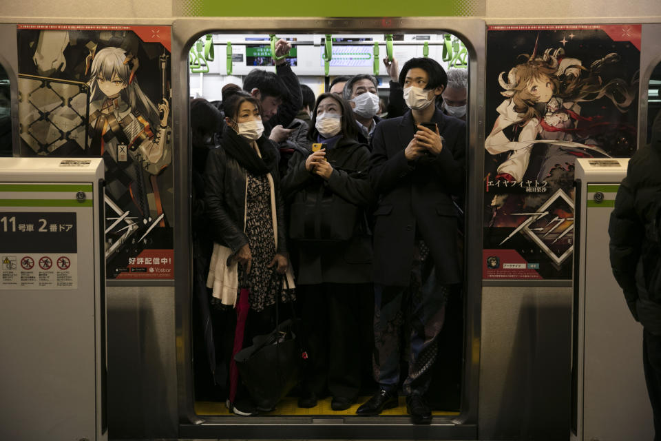 FILE - In this March 2, 2020, file photo, commuters wearing masks stand in a packed train at the Shinagawa Station in Tokyo. During commuting hours, almost everyone on public transportation wears a mask. (AP Photo/Jae C. Hong, File)