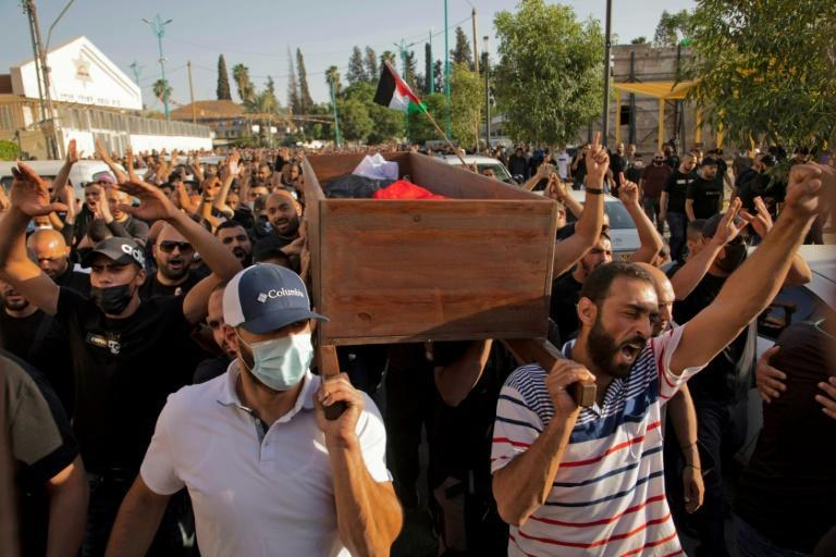Arab Israelis gesture and wave Palestinian flags during the funeral of Musa Hassuna in the central Israeli city of Lod