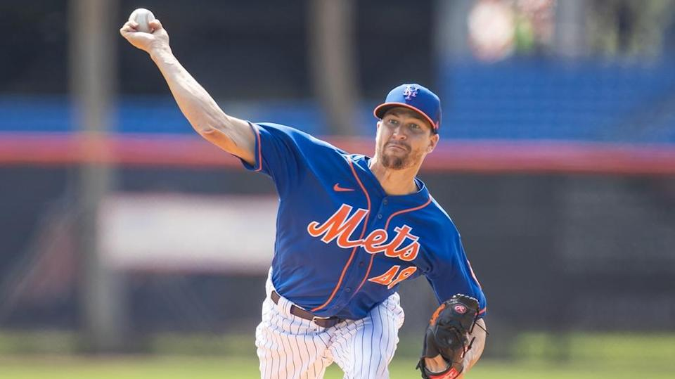 Jacob deGrom fires a pitch during spring training wearing blue jersey, close crop