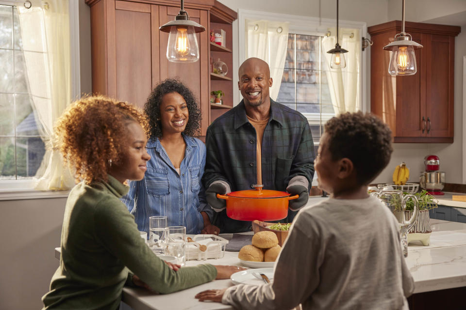 Family making meals together in the kitchen with a dutch oven