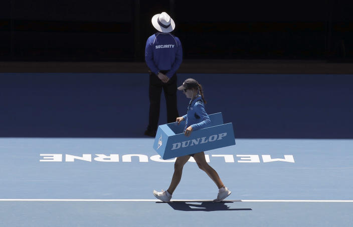 FILE In this Jan. 22, 2019 file photo, A line judge crosses the court during a break in the quarterfinal between Spain's Roberto Bautista Agut and Greece's Stefanos Tsitsipas at the Australian Open tennis championships in Melbourne, Australia. In a Grand Slam-first, at the 2021 Australian Open tennis championships, there will be no on-court line judges on any of the tournament courts in an effort to reduce the number of staff on-site due to coronavirus-related concerns. Only chair umpires and ball persons will be on the court. (AP Photo/Aaron Favila,File)
