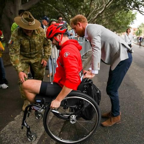Prince Harry helps a competitor up a walkway - Credit: Reuters