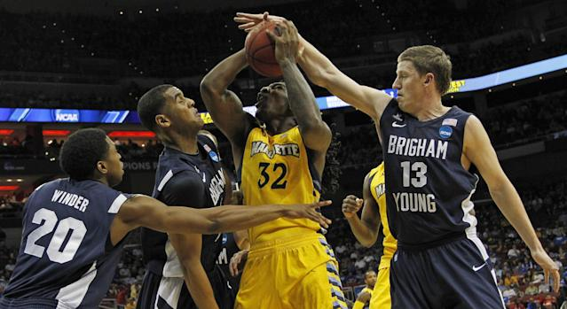 Marquette forward Jae Crowder (32) goes to the basket against the defense of BYU's guard Anson Winder (20), forward Brandon Davies (0) and guard/forward Brock Zylstra (13) in the first half of their NCAA tournament second-round college basketball game in Louisville, Ky., Thursday, March 15, 2012. (AP Photo/Dave Martin)