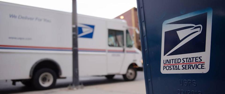 united states postal service truck on street in front of a letter box