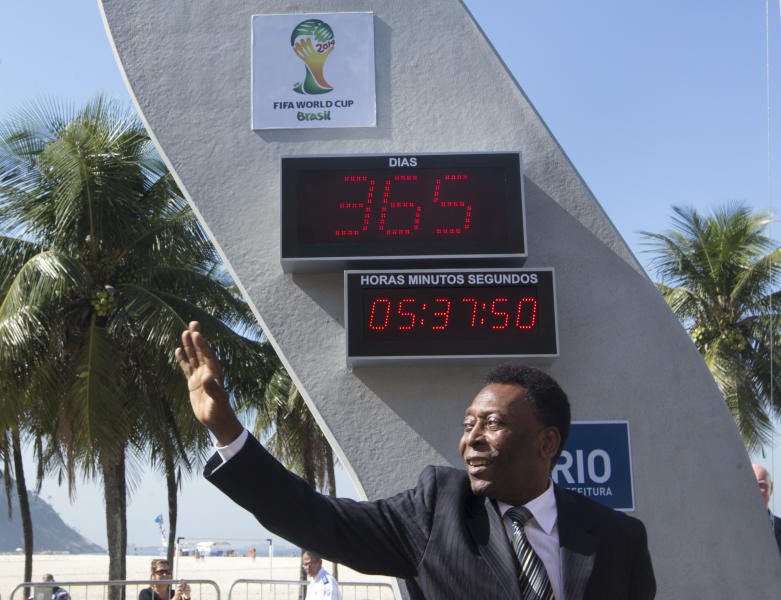 Brazilian football icon Pele waves during the unveiling of the Hublot Countdown Clock designed by the late architect Oscar Niemeyer, at the Copacabana beach in Rio de Janeiro, Brazil, Wednesday, June 12, 2013. The event marks the start of the one-year countdown to the opening 2014 World Cup game in Brazil. (AP Photo/Silvia Izquierdo)
