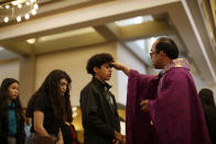 A priest marks repentance ashes on the foreheads of students from the St. John Paul II Catholic High School during Ash Wednesday Mass at the St. Thomas Aquinas church in Phoenix, Ariz., on Feb. 26, 2020. (AP Photo/Dario Lopez-MIlls)