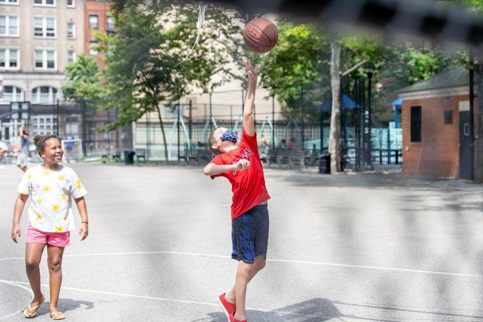 """<p>A young boy plays basketball on playground in Chelsea, New York. Schools across the country are grappling with plans for the return to school during the COVID-19 pandemic. </p><p><strong>RELATED:</strong> <a href=""""https://www.goodhousekeeping.com/health/a33251177/is-it-safe-to-go-back-to-school-coronavirus/"""" rel=""""nofollow noopener"""" target=""""_blank"""" data-ylk=""""slk:Is It Safe for Kids to Go Back to School During a Pandemic?"""" class=""""link rapid-noclick-resp"""">Is It Safe for Kids to Go Back to School During a Pandemic?</a></p>"""