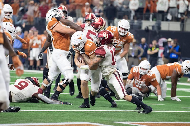 Texas Longhorns quarterback Sam Ehlinger (#11) fights his way into the end zone as Oklahoma Sooners linebacker Curtis Bolton (#18) tries to make the tackle during last season's Big 12 Championship game. (Getty)