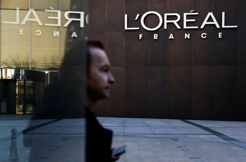 FILE PHOTO: A man walks by the logo of French cosmetics group L'Oreal in the western Paris suburb of Levallois-Perret