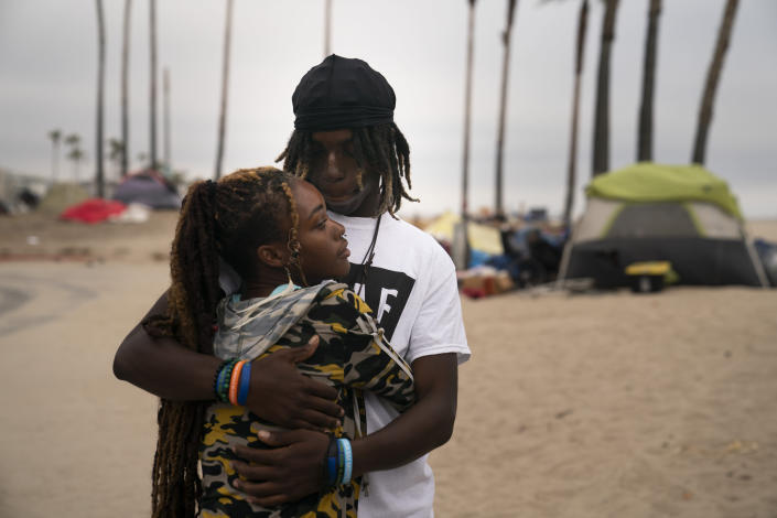 Yahto Bank and his girlfriend, Nas, a couple living in an homeless encampment set up along the Venice Beach boardwalk, embrace each other while waiting to pick up free meals in the Venice neighborhood of Los Angeles, Tuesday, June 29, 2021. (AP Photo/Jae C. Hong)