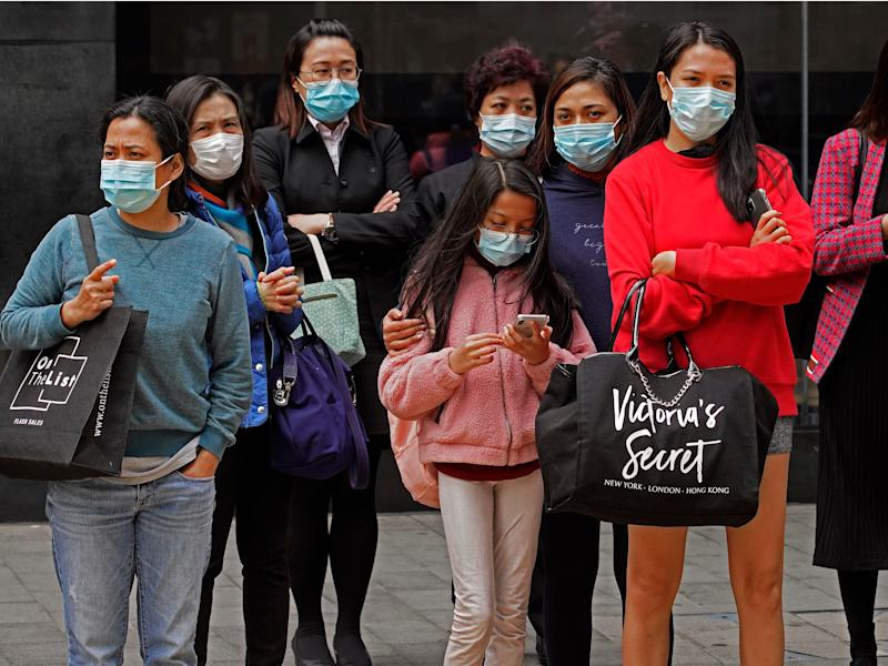 People wear protective face masks on a street corner in Hong Kong, Monday, Feb. 3, 2020. In Hong Kong, thousands of health care workers were threatening to go on strike Tuesday unless the government agrees to talks before a 6 p.m. Monday deadline. Hong Kong has recorded 14 cases of the virus and has cut flights and train and bus connections to the mainland, but a push is growing for the semi-autonomous Chinese city to close the border completely. (AP Photo/Vincent Yu)