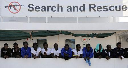 FILE PHOTO: Migrants wait to disembark from the Aquarius ship in the Sicilian harbour of Palermo, Italy October 13, 2017. REUTERS/Guglielmo Mangiapane