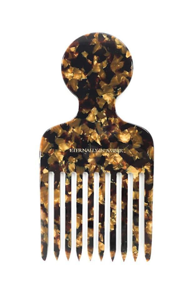 """<p>Eternally in Amber Signature Black/Gold Granite Hair Pick, $20, <a href=""""https://www.eternallyinambershop.com/product/signature-black-gold-granite-hair-pick/256?cs=true"""" rel=""""nofollow noopener"""" target=""""_blank"""" data-ylk=""""slk:available here"""" class=""""link rapid-noclick-resp"""">available here</a>.</p>"""