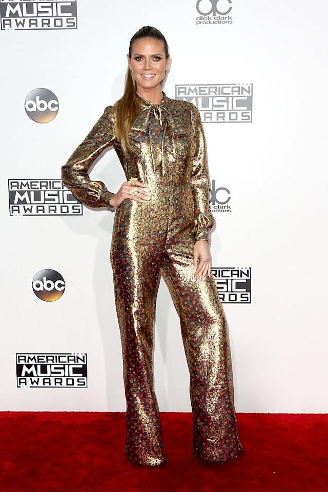 <p>Was Heidi Klum just wearing the latest trend or sending a message with her gold pussybow jumpsuit? <em>(Photo: Getty Images)</em> </p>