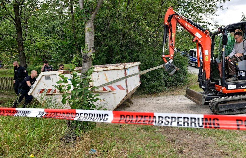 Germany police officers remove a container during a search at an allotment garden plot in Seelze (AP)