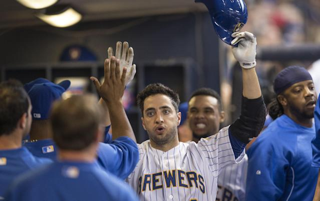 Milwaukee Brewers' Ryan Braun is greeted by teammates after scoring against the Pittsburgh Pirates during the fourth inning of a baseball game on Sunday, April 13, 2014, in Milwaukee. (AP Photo/Tom Lynn)