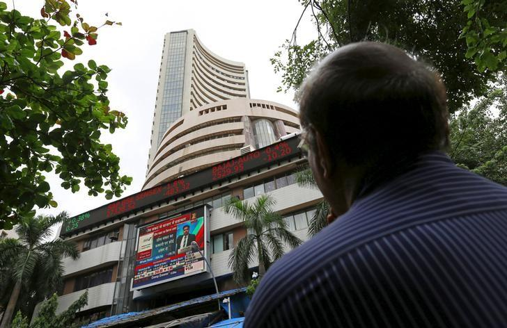 A man looks at a screen across a road displaying the Sensex on the facade of the Bombay Stock Exchange (BSE) building in Mumbai, India, June 29, 2015. REUTERS/Danish Siddiqui/File Photo