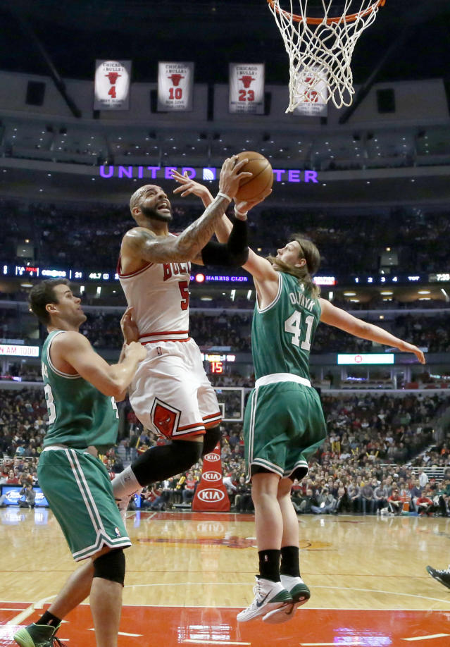 Chicago Bulls power forward Carlos Boozer (5) scores between Boston Celtics power forward Kris Humphries, left, and Kelly Olynyk (41) during the first half of an NBA basketball game on Thursday, Jan. 2, 2014, in Chicago. (AP Photo/Charles Rex Arbogast)