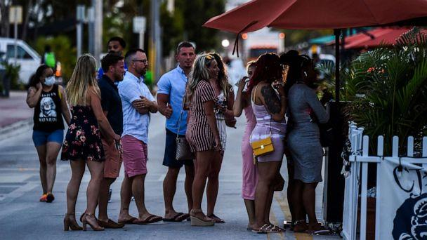 PHOTO: People stand in queue to enter a restaurant on Ocean Drive in Miami Beach, Florida, on June 26, 2020. (Chandan Khanna/AFP via Getty Images)