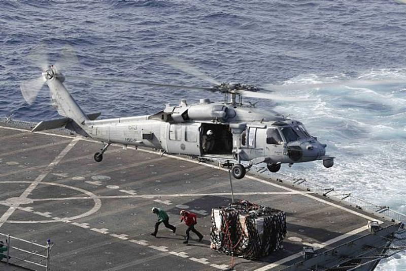 In this Sunday, May 19, 2019 photo, an MH-60S Sea Hawk helicopter transports cargo from the fast combat support ship USNS Arctic to the Nimitz-class aircraft carrier USS Abraham Lincoln during a replenishment-at-sea operation in the Arabian Sea, as Mideast tensions remain high between Tehran and the United States. (Mass Communication Specialist 3rd Class Darion Chanelle Triplett/U.S. Navy via AP)
