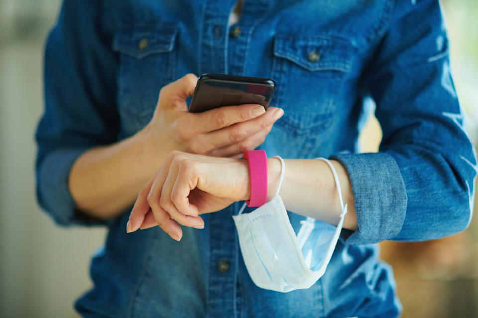 Closeup on modern middle age housewife with a smartphone and fitness tracker checking daily step stats in the house. Weight control on coronavirus quarantine concept