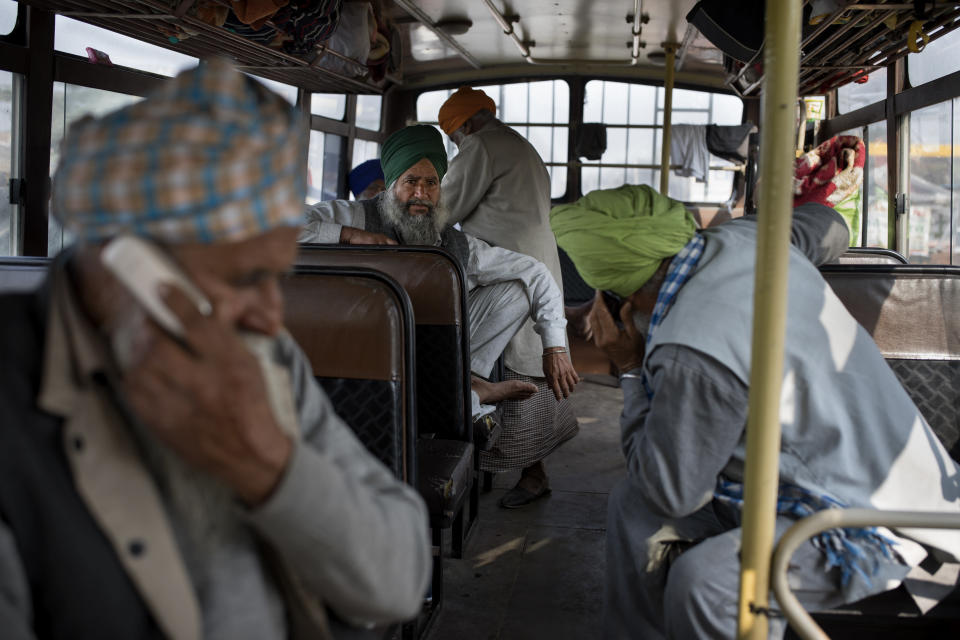 "Protesting farmers speak on their mobile phones as they sit inside a school bus in which they traveled to this protest site, at the Delhi-Haryana state border, India, Tuesday, Dec. 1, 2020. The busy, nonstop, arterial highways that connect most northern Indian towns to this city of 29 million people, now beat to the rhythm of never-heard-before cries of ""Inquilab Zindabad"" (""Long live the revolution""). Tens and thousands of farmers, with colorful distinctive turbans and long, flowing beards, have descended upon its borders where they commandeer wide swathes of roads. (AP Photo/Altaf Qadri)"