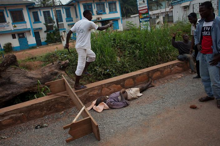 A man runs past a body to strike another man, as tensions flared in central Bangui, Central African Republic, Thursday, Dec. 26, 2013. The spokesman for an African Union peacekeeping force says six Chadian peacekeepers were killed and 15 were wounded, after being attacked Wednesday. The Chadian contingent, which is made up of Arabic-speaking Muslim soldiers, has been accused of taking sides against the Christian population in the country's sectarian conflict. (AP Photo/Rebecca Blackwell)