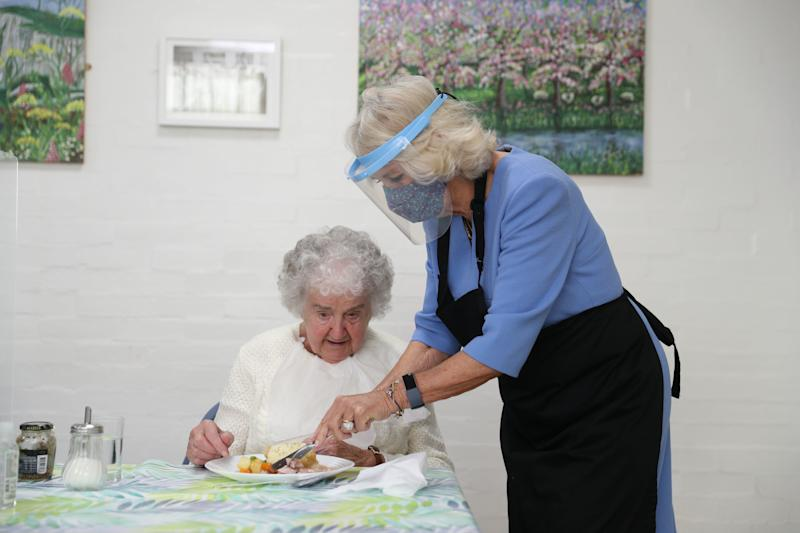 Britain's Camilla, Duchess of Cornwall, in her role as President, Royal Voluntary Service, wears a facemask and faceshield as she serves lunch during her visit to the Royal Voluntary Service Mill End lunch club in Rickmansworth, Hertfordshire on October 8, 2020, to meet volunteers who have overcome recent challenges posed by the novel coronavirus COVID-19 pandemic to reinstate the much-needed lunch sessions. (Photo by Andrew Matthews / POOL / AFP) (Photo by ANDREW MATTHEWS/POOL/AFP via Getty Images)