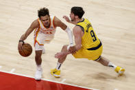 Atlanta Hawks guard Trae Young (11) tries to get around Indiana Pacers guard T.J. McConnell (9) as he brings the ball up during the fourth quarter of an NBA basketball game Saturday, Feb. 13, 2021, in Atlanta. (AP Photo/Butch Dill)