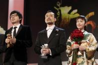 """Diao Yinan director of """"Bai Ri Yan Huo"""" (Black Coal, Thin Ice) poses with his Golden Bear for Best Film next to actor Liao Fan (C) who poses with his Silver Bear for Best Actor, and actress Haru Kuroki (R) who holds her Silver Bear for Best Actress, during the awards ceremony of the 64th Berlinale International Film Festival in Berlin February 15, 2014. REUTERS/Tobias Schwarz"""