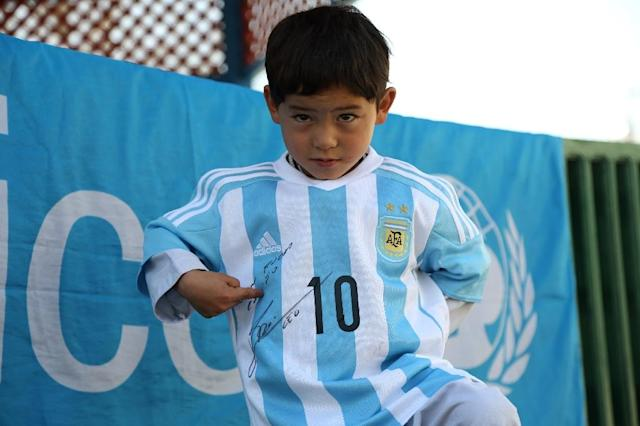 Afghan boy Murtaza Ahmadi proudly wears one of the jerseys sent by his idol Lionel Messi (AFP Photo/Mahdy Mehraeen)