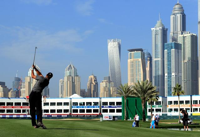 Tiger Woods from the U.S. follows through a shot on the 18th hole during the first round of the Dubai Desert Classic golf tournament in Dubai, United Arab Emirates, Thursday, Jan. 30, 2014. (AP Photo)