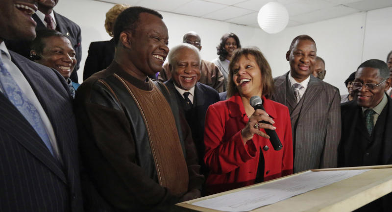 In this Feb. 7, 2013 photo, from left Gail Mahome, Dr. Willie Wilson and Dr. John Gray, smile at a news conference in Chicago, as they join other members of the International Ministers & Community Alliance in endorsing Robin Kelly, center, a former Illinois state representative and Democratic hopeful running in a special primary election  Feb. 26 for Illinois' 2nd District seat to replace Jesse Jackson Jr. who resigned in November 2012. Like much of the national conversation these days, the race to replace Jackson Congress has been dominated by one topic: guns. Nearly half of 2nd District voters live on the South Side of Chicago, where some of the nation's worst gun violence has been heavily concentrated. (AP Photo/M. Spencer Green)