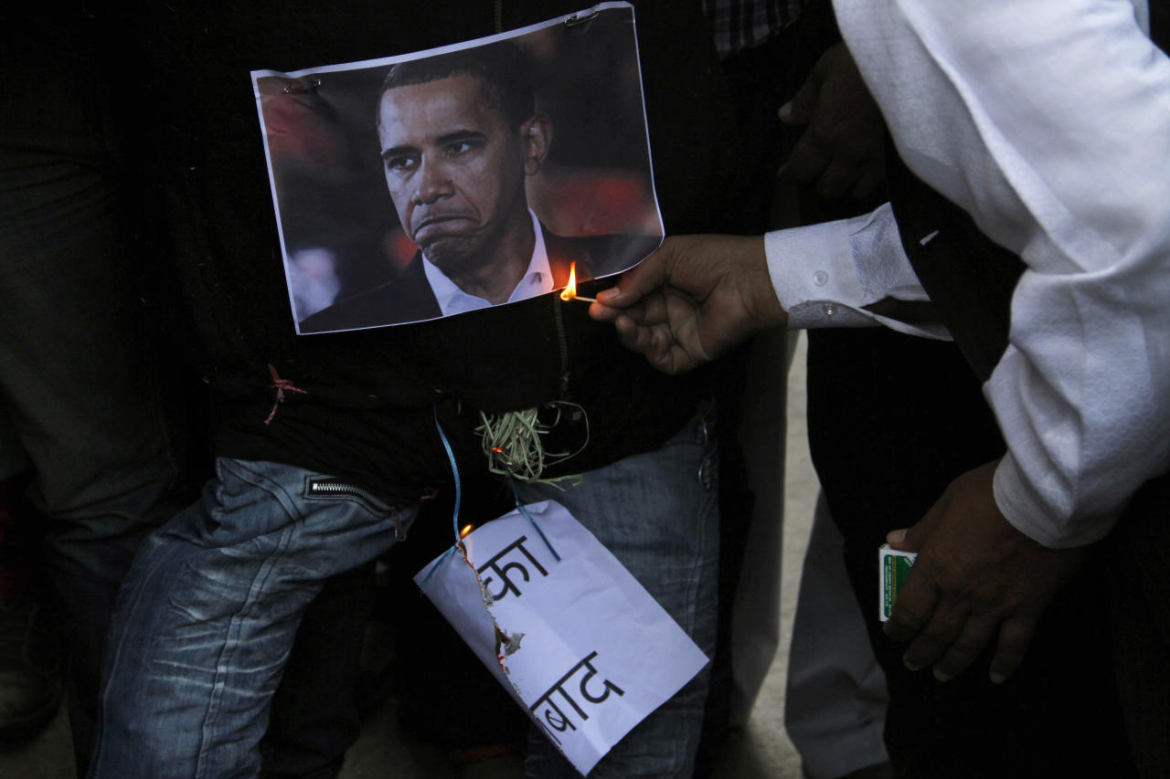 An Indian Muslims burns an effigy of U.S. President Barack Obama as he and others protest against the alleged mistreatment of New York based Indian diplomat Devyani Khobragade, in Ajmer, India, Thursday, Dec. 19, 2013. The case has sparked a diplomatic furor between the United States and India, which is incensed over what its officials described as degrading treatment towards India's deputy consul general in New York. (AP Photo/Deepak Sharma)