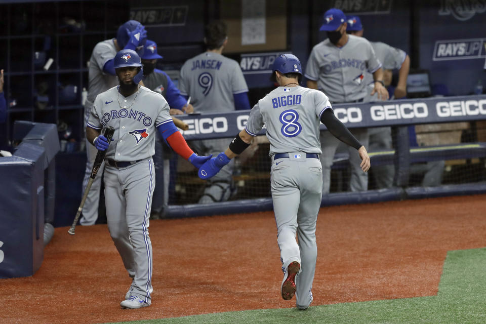 Toronto Blue Jays' Cavan Biggio (8) celebrates with on-deck batter Teoscar Hernandez after scoring on a hit by Randal Grichuk during the fourth inning of a baseball game against the Tampa Bay Rays Friday, July 24, 2020, in St. Petersburg, Fla. (AP Photo/Chris O'Meara)