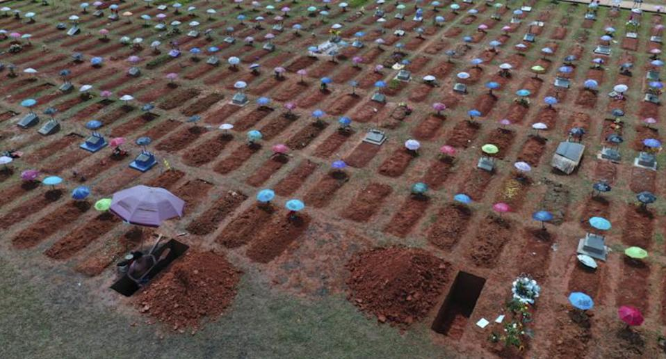 A worker digs a grave in the San Juan Bautista cemetery in Iquitos, Peru.
