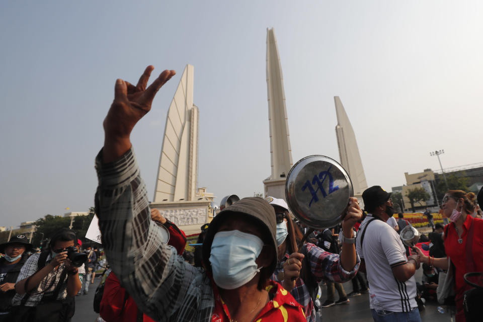 A pro-democracy protester flashes the three-finger protest gesture during a rally at Democracy Monument in Bangkok, Thailand, Saturday, Feb. 13, 2021. The rally in the Thai capital was organized by the Ratsadorn movement, which campaigned last year for Prime Minister Prayuth Chan-ocha and his government to step down, the constitution to be amended and the reform of the monarchy to make it more accountable. (AP Photo/Sakchai Lalit)