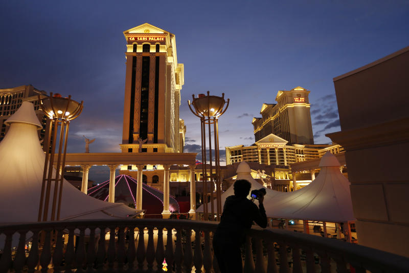 FILE - In this Monday, Jan. 12, 2015, file photo, a man takes pictures of Caesars Palace hotel and casino, in Las Vegas. Billionaire investor Carl Icahn plans to drive casino giant Caesars Entertainment to sell itself. The activist investor disclosed in a securities filing Tuesday, Feb. 19, 2019, that he owns a roughly 10 percent stake in the company, confirming previous reports. (AP Photo/John Locher, File)